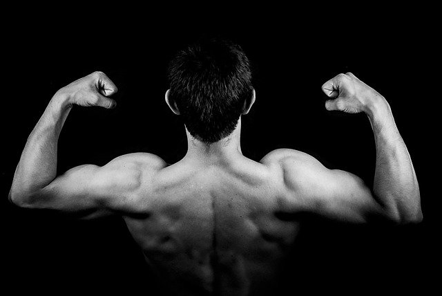 Muž so svalmi v póze v tme
