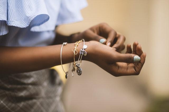 Žena s farebnou manikúrou má na ruke zlaté s strieborné šperky